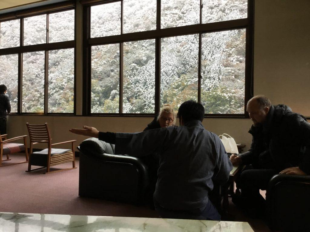 箱根・豊栄荘のロビーでデンマークから来たお客さまに英語で説明をしている様子。